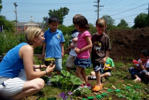 Woman teaches children about gardening.