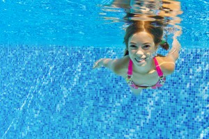 Girl swimming underwater in a pool.