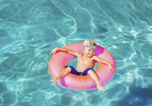 Young boy floating in an inner tube, in a pool.