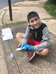 Youth marking one of Arlington's storm drains.