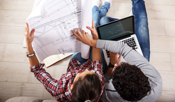 Young couple examining blueprints of they new house.