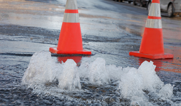 Construction cones around a water main break in the road.