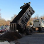 Truck dumping a full size load of mulch.