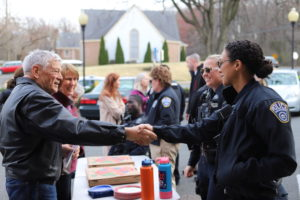 officers and citizens shaking hands at a community event
