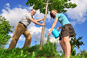 a father and daughter watering a tree