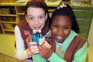 Two girl scouts holding crafts.