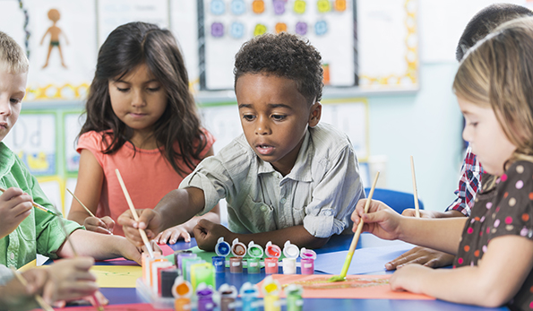A group of preschool or kindergarten children in art class painting pictures at a table. A little African American boy, 6 years old, is in the middle, reaching over to dip his brush in the paint.