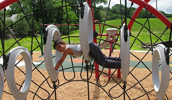 boy playing on playground at Drew