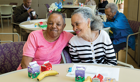image of two 55+ smiling and bonding over lunch