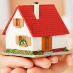 Close-up of woman's hands holding a small model house. Horizontal shot. Isolated on white.