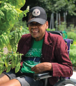 accessible garden, smiling man gardening in wheelchair.