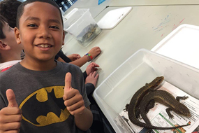 boy standing next to two lizards giving thumbs up