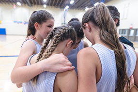 Girls basketball coach leads a pre-game huddle
