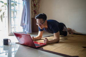 An Asia Chinese businessman work from home. Plank workout and work at the same time