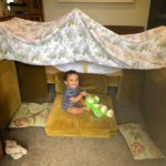 Couch fort with baby and toy