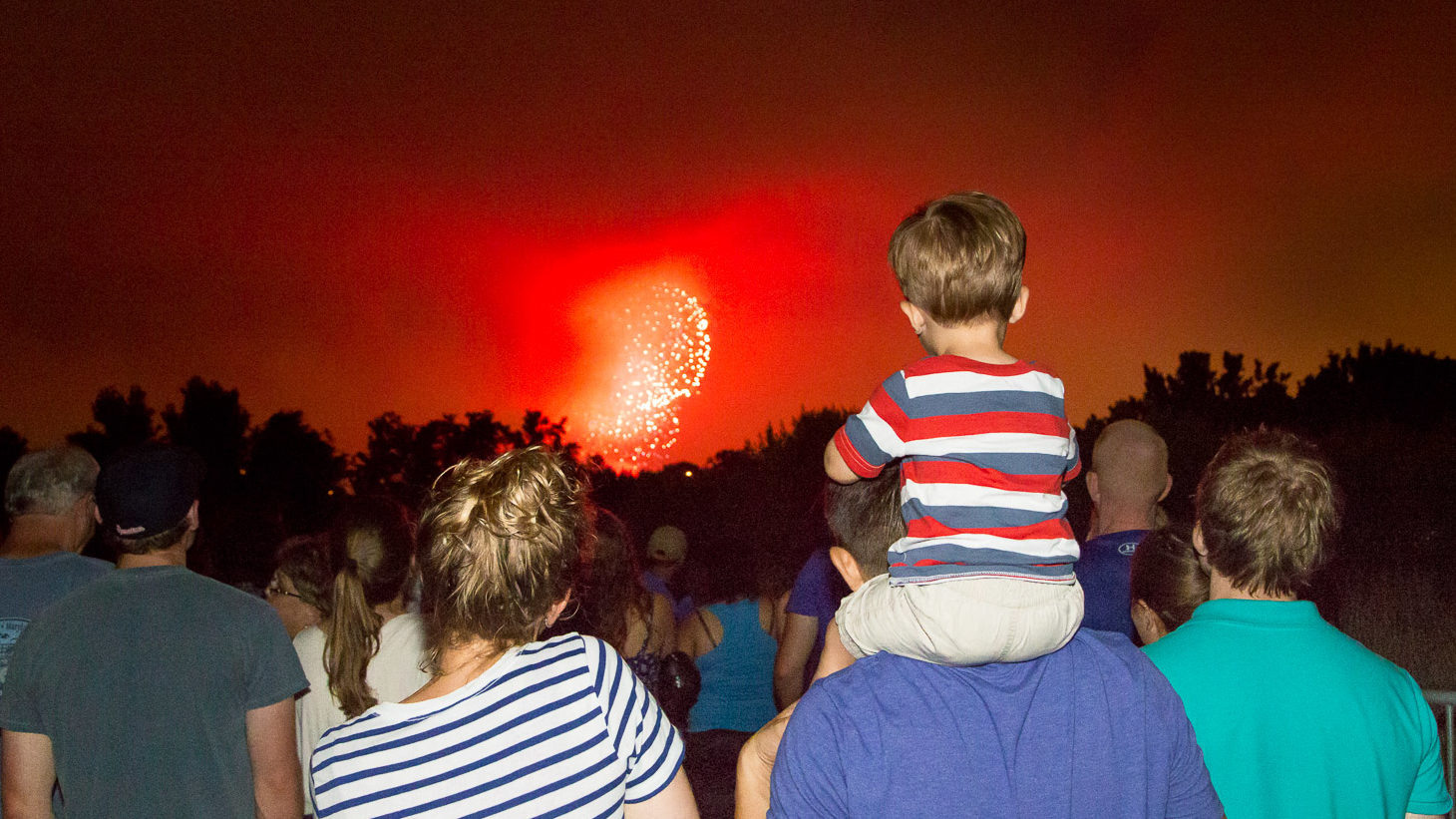 boy on dads shoulders watching 4th of july fireworks