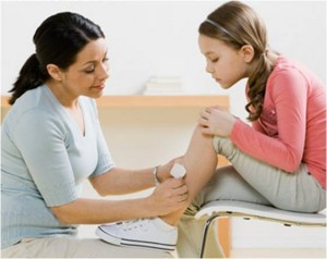 School nurse bandaging a girl's injury.