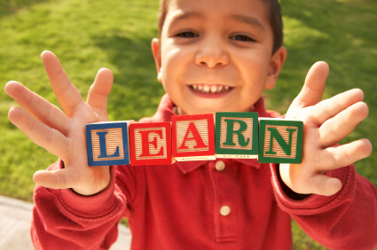 Child holding blocks that say learn