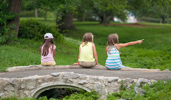 girls sitting on bridge