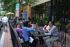 group of people eating lunch together on a sidewalk cafe in the shirlington neighborhood