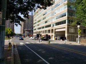 Two people cross N Quincy Street at 10th St N