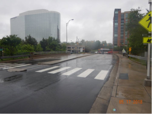 Shirlington Road looking south from 27th St. The bridge and pedestrian crossing are visible, as are some larger buildings.