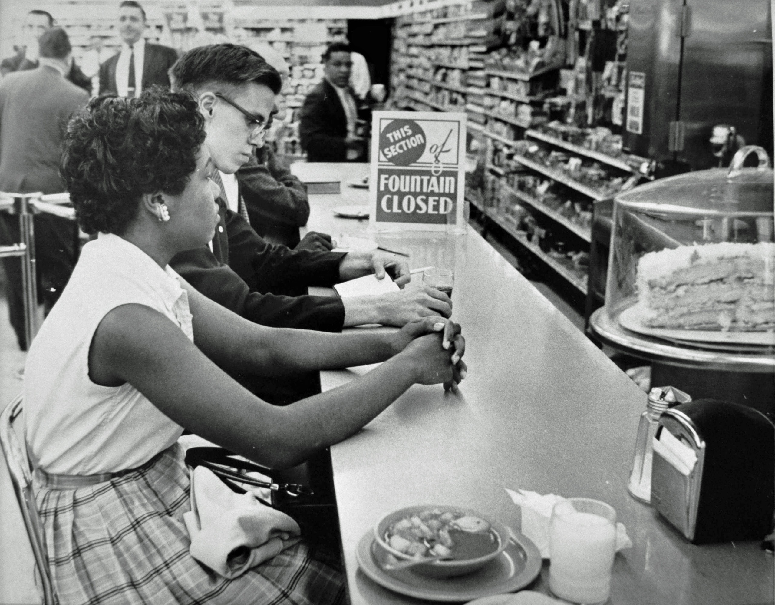 Gwendolyn Greene and David Hartsough sit at the People's Drug Store counter.
