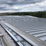 Standing metal seam roof installation over the 50M pool area.