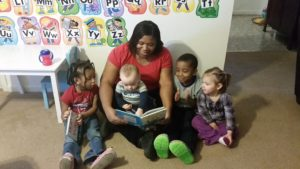 child care instructor reading to four kids on the floor