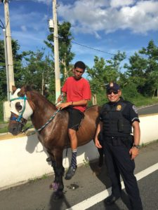 police officer poses with Puerto Rico child on horse