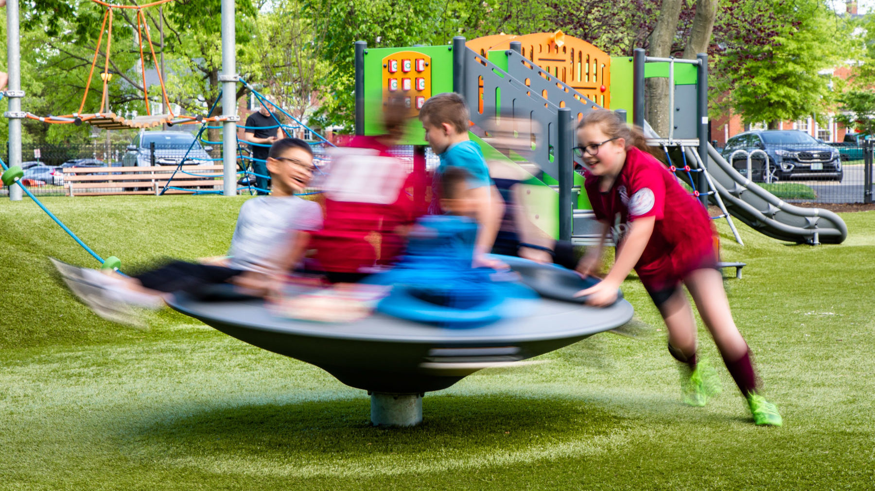 A group of six children in blue and red shirts are playing on a piece of spinning playground equipment, surrounded by green grass and with a large set of orange and green playground equipment in the background.