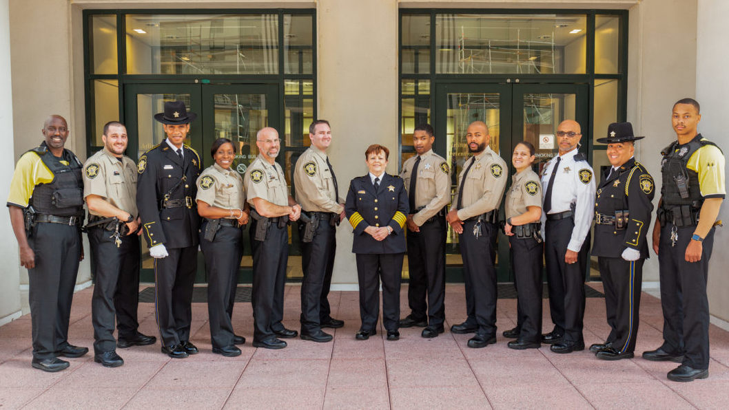 Sheriff Beth Arthur is flanked by 12 deputies and other personnel, each wearing a different uniform combination allowed under the Sheriff's Office's official uniform change effective Sept. 1, 2019.