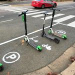 """Three scooters in an Arlington """"scooter corral."""""""