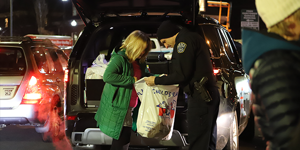 officer receives toys from a donor at the fill the cruiser holiday toy drive