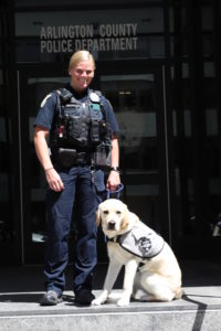 Officer and service dog outside police department