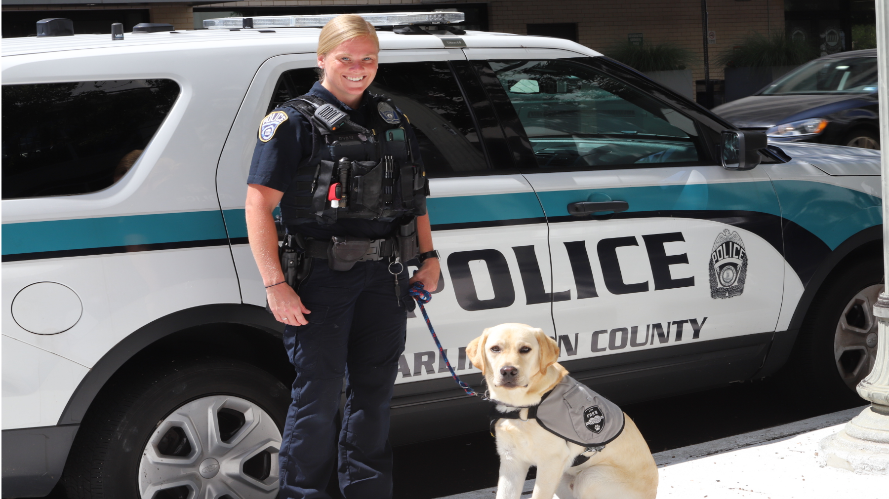 Officer with service dog in front of cruiser